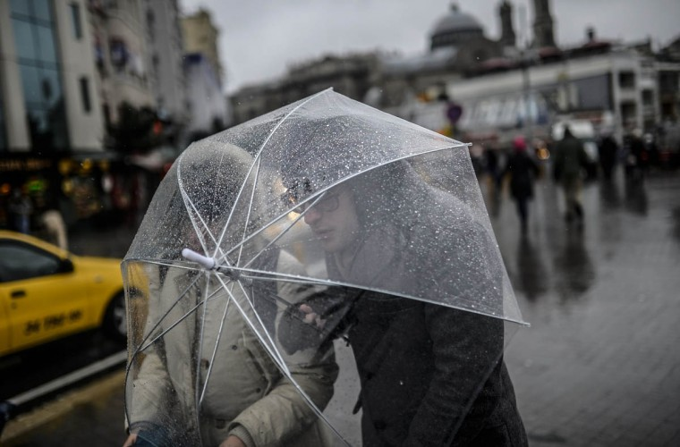 People try to make their way on Istiklal Avenue during a storm on December 31, 2014 in Istanbul. (Bulent Kilic/Getty Images)