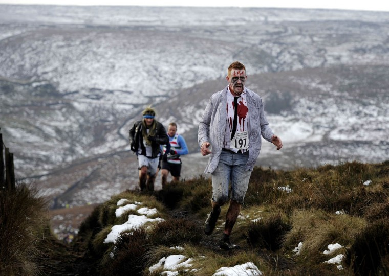 Runners in fancy dress cross the Pennine hills near Haworth,northern England in the traditional Auld Lang Syne Fell race which attracts hundreds of runners many in costume Wednesday Dec. 31, 2014. (John Giles/AP photo)