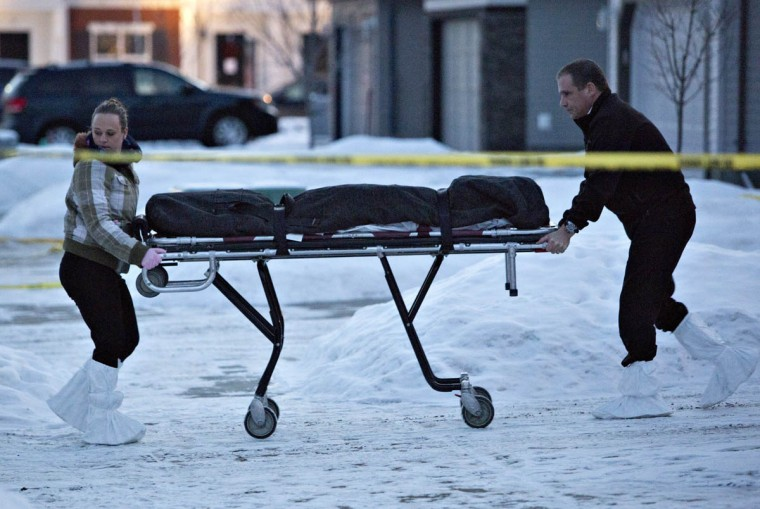 """The body of a victim is carried out of a north Edmonton home in Edmonton, Alberta, Tuesday, Dec. 30, 2014. Nine people, including seven adults and two young children, were found dead at three separate crime scenes in what Edmonton's police chief on Tuesday called a """"senseless mass murder."""" (Jason Franson/AP photo)"""