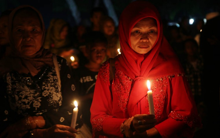 Indonesian women hold candles to pray for the victims of AirAsia Flight 8501 in Pangkalan Bun, Indonesia, Thursday, Jan 1, 2015. A massive hunt for the victims of the jet resumed in the Java Sea on Wednesday, but wind, strong currents and high surf hampered recovery efforts as distraught family members anxiously waited to identify their loved ones. (Tatan Syuflana/AP photo)