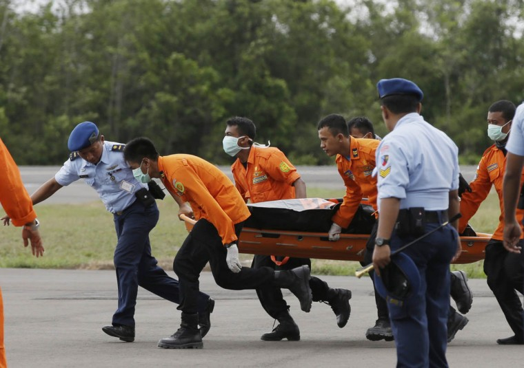 Officers of the National Search And Rescue Agency (BASARNAS) carry a body of one of the victims on board the ill-fated AirAsia Flight 8501, from a helicopter upon arrival at the airport in Pangkalan Bun, Indonesia, Wednesday, Dec. 31, 2014. A massive hunt for the victims of the jet resumed in the Java Sea on Wednesday, but wind, strong currents and high surf hampered recovery efforts as distraught family members anxiously waited to identify their loved ones. (Achmad Ibrahim/AP photo)