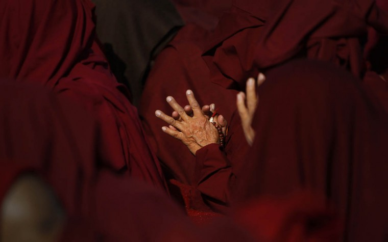 A Buddhist monk participates in Nyigma Monlam prayers at the Boudhanath Stupa in Katmandu, Nepal, Wednesday, Dec. 31, 2014. The Nyigma Monlam is an annual prayer for world peace. (Niranjan Shrestha/AP photo)