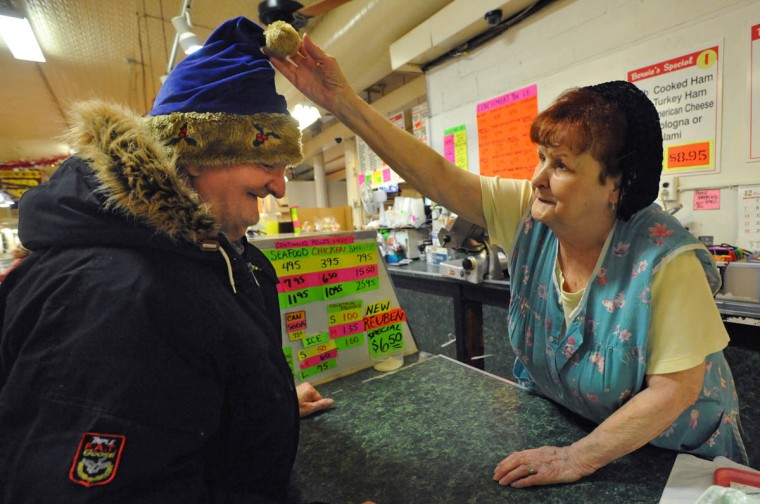 Elsie Wade, who has worked at Hollins Market for 35 years, adjusts the pom pom on Timmy Bailey's hat. Bailey has worked at the market since he was a teenager, taking out the trash for the vendors. Wade has worked at Bernie's Deli for 14 years. Previously she worked at Sophie's Bakery and Mike's Lunch. (Amy Davis, Baltimore Sun)