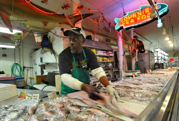 Tyrone Johnson has worked at Johnnie's Seafood at the Hollins Market for over 20 years. Johnnie's Seafood has been owned by Abraham Kim for 28 years. (Amy Davis, Baltimore Sun)