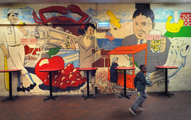 A boy runs past a mural, probably painted over thirty years ago, at the Hollins Market. Famous Baltimoreans depicted who hailed from the vicinity of the market include, from left, Babe Ruth, Edgar Allan Poe, and H.L. Mencken. (Amy Davis, Baltimore Sun)