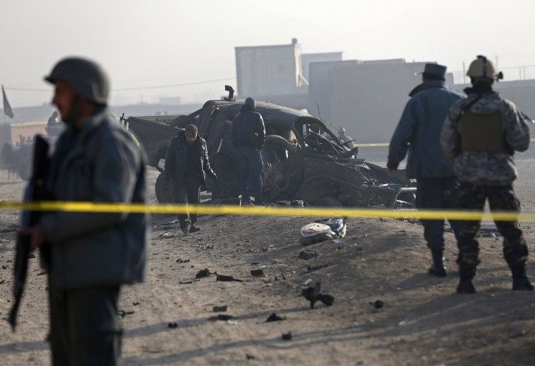 Afghan security forces inspect at the site of a suicide attack in Kabul December 18, 2014. One policeman was killed and two were injured on the outskirts of the Afghan capital on Thursday, in a blast caused by a suicide bomber attempting to enter Kabul in a vehicle laden with explosives, an interior ministry spokesman said. REUTERS/Omar Sobhani