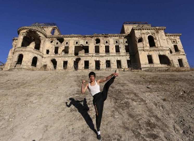 Abbas Alizada, who calls himself the Afghan Bruce Lee, poses for the media in front of the destroyed Darul Aman Palace in Kabul December 9, 2014. (Mohammad Ismail/Reuters)