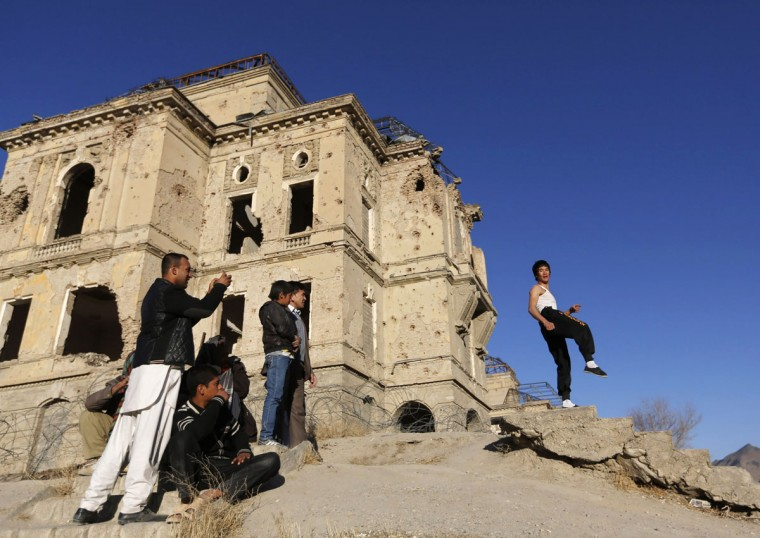 Abbas Alizada, who calls himself the Afghan Bruce Lee (R), poses for the media in front of the destroyed Darul Aman Palace in Kabul December 9, 2014. (Mohammad Ismail/Reuters)