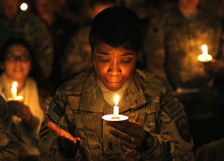 U.S. troops from the Nato-led International Security Assistance Force (ISAF) light candles during Christmas Eve celebrations at Bagram Airfield, north of Kabul. (Mohammad Ismail, Reuters photo)