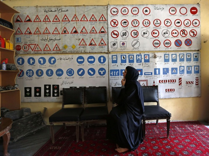 A women attends a class at a driving school in Kabul August 17, 2014. Kabul is one of the world's fastest growing cities and its streets are increasingly blocked by cars and buses. In the city's private driving schools, students pay a $60 fee for a 45-day course, which includes oral and practical driving tests at the country's Traffic Department. Some of the women who have signed up say learning to drive is a way to escape unwanted gazes and physical harassment on the cramped, crowded minibuses that are often the only method of urban public transport. REUTERS/Mohammad Ismail