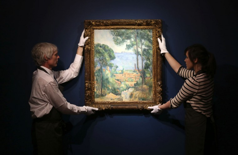 "Christie's staff members pose for a photograph with ""Vue sur L'Estaque et Le Chateau d'If"" by Paul Cezanne in London December 17, 2014. The ""shimmering"" Paul Cezanne painting of the Mediterranean with a castle in the background is expected to attract the big-money buyers at a February auction that includes works by Modigliani, Giacometti and Picasso, Christie's said on Wednesday. The Cezanne work, ""Vue sur L'Estaque et Le Chateau d'If"", which he painted in 1883-85 from an apartment overlooking Marseille harbour, will be auctioned on Feb. 4. REUTERS/Paul Hackett"