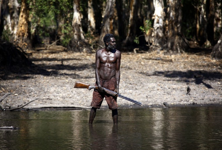 Australian Aboriginal hunter Roy Gaykamangu of the Yolngu people stands in a billabong after shooting a crocodile near the 'out station' of Yathalamarra, located on the outskirts of the community of Ramingining in East Arnhem Land. (David Gray/Reuters)
