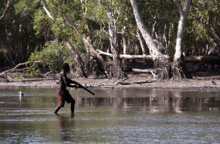 Australian Aboriginal hunter Roy Gaykamangu of the Yolngu people walks across a billabong while hunting a crocodile near the 'out station' of Yathalamarra, located on the outskirts of the community of Ramingining in East Arnhem Land. (David Gray/Reuters)