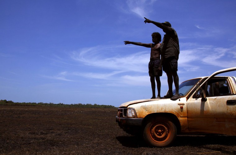 Australian Aboriginal hunters Bruce (L) and Robert Gaykamangu of the Yolngu people stand on the bonnet of their car looking for potential prey at a billabong near the 'out station' of Ngangalala, located on the outskirts of the community of Ramingining in East Arnhem Land. (David Gray/Reuters)