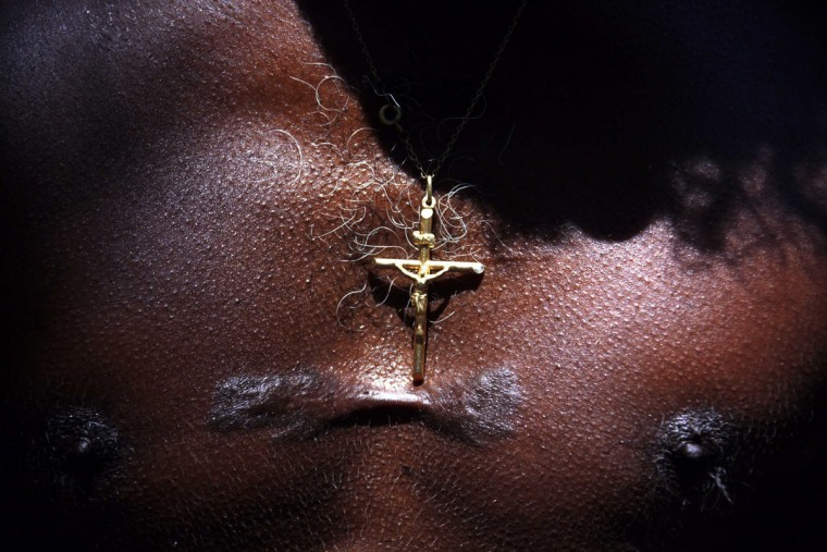 Australian Aboriginal hunter Bruce Gaykamangu of the Yolngu people wears a crucifix that sits just above his initiation scar while searching for Magpie Geese near the community of Ramingining in East Arnhem Land. (David Gray/Reuters)