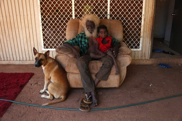 Robin Mildjingi and his grandson Gasier of the Yolngu people pose for a photograph as they sit out the front of their house in the Australian Aboriginal community of Ramingining located in East Arnhem Land. (David Gray/Reuters)