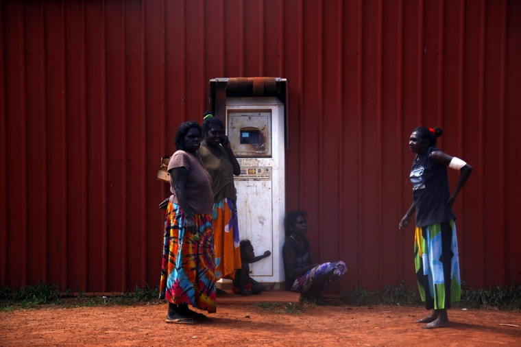 Members of the Australian Aboriginal community of Ramingining stand next to a machine used to pay for fuel in East Arnhem Land. (David Gray/Reuters)