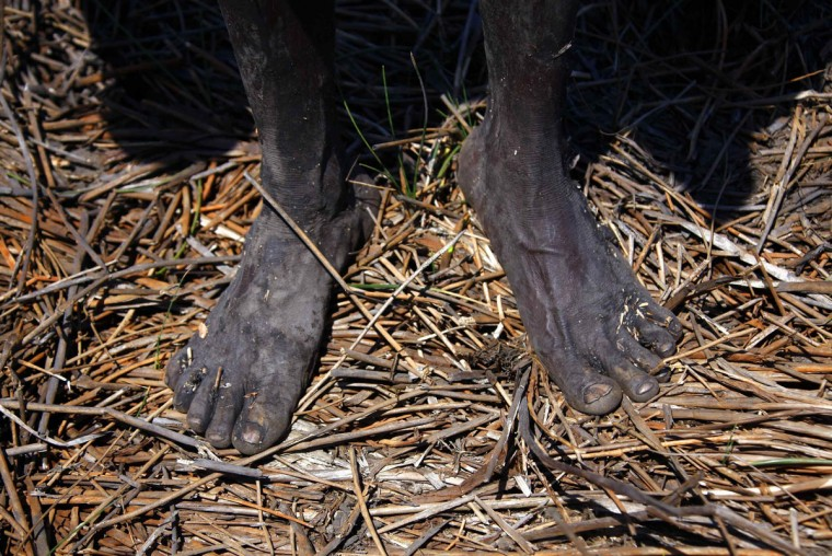 The bare feet of Australian Aboriginal hunter Robert Gaykamangu of the Yolngu people can be seen as he stands next to a billabong near the 'out station' of Ngangalala, on the outskirts of the community of Ramingining in East Arnhem Land . (David Gray/Reuters)