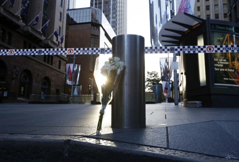 A bouquet is pictured under police tape near the cordoned-off scene of a hostage taking at Martin Place after it ended early December 16, 2014. Heavily armed Australian police stormed a Sydney cafe on Tuesday and freed a number of hostages being held there at gunpoint, in a dramatic end to a 16-hour siege in which three people were killed and four wounded. (Jason Reed /Reuters)