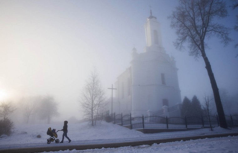 A woman pushes a pram with a child as heavy fog covered streets in a small town of Zaslavl, northwest of Minsk. (Vasily Fedosenko/Reuters photo)