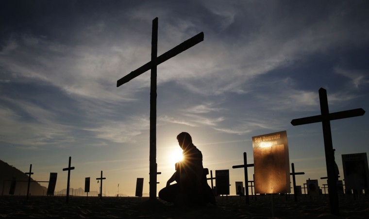 A police officer kneels among crosses planted by the NGO Rio de Paz (Peace Rio) on Copacabana beach, in memory of police officers killed in Rio de Janeiro December 9, 2014. Rio de Paz placed 152 black crosses symbolizing the number of police officers killed in the last two years in Rio de Janeiro, according to NGO. (Sergio Moraes/Reuters)