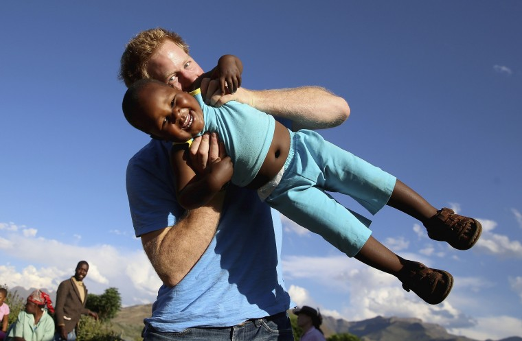 Britain's Prince Harry swings three-year-old orphan boy Lerato, in this photograph taken with the help of three-year-old blind girl Karabo, during a visit to Phelisanong Children's Home in Maseru December 6, 2014. Prince Harry was visiting Lesotho to see the work of his charity Sentebale, which provides healthcare and education to vulnerable children. The prince was with Lerato, who was abandoned at birth, when Karabo heard the clicking sounds of a camera and decided to walk over and shoot the photo with a bit of help from a photographer. Picture taken on December 6 and released to Reuters on December 18. REUTERS/Chris Jackson/Pool
