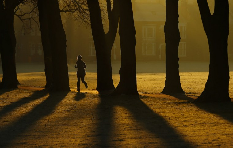 A woman runs through Victoria Park at sunrise in Leicester, central England, December 30, 2014. (Darren Staples/Reuters)