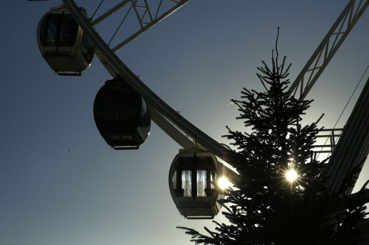The sun shines through a Christmas Tree next the to the Brighton Wheel in Brighton, southern England December 16, 2014. (REUTERS/Luke MacGregor)