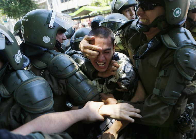 A student is detained during a demonstration near the Ministry of Education at Santiago, December 18, 2014. Students were protesting on Thursday against the increase in tariffs at their universities. REUTERS/Ivan Alvarado
