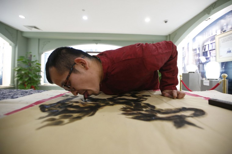 Folk artist Han Xiaoming demonstrates painting with his tongue in Hangzhou, Zhejiang province December 4, 2014. Han dips his tongue in ink to paint on paper, and uses his fingers to fill in final adjustments. The artist also uses a paintbrush held with his mouth and utilizes fish and vegetables as paint tools, local media reported. REUTERS/Aly Song