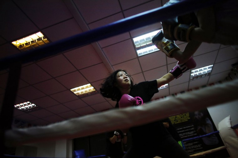 "A woman punches during a boxing class at Princess Women's Boxing Club in Shanghai. Women have boxed as long as the sport has existed but for years they were relegated out of national and international competitions in many countries around the world. Female boxers entered the ring in an exhibition match at the 1904 Olympic Games, but it was more than a century later when they were given the green light to make their Olympic debut in London in 2012. In China, although there is a long history of lightweight Chinese fighters, the sport is not very popular among women. However in 2010, Gong Jin, a woman who has trained since she was 12 years old, founded Princess Women's Boxing Club, the first ""only for women"" boxing club in China. Today more than 100 students between the ages of 18 and 40 train at the small studio in downtown Shanghai. (Carlos Barria/Reuters)"