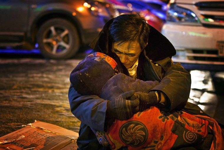 A man, whose surname is He, cuddles the body of his dead wife during a sub-zero evening in Shenyang, Liaoning province December 17, 2014. The man sat by the roadside while holding his wife's body for almost two hours till his son came and persuaded him to bring the body home, according to local media. The wife had just bought medicine from a pharmacy when she collapsed in a street and died of heart failure. Picture taken December 17. REUTERS/Stringer