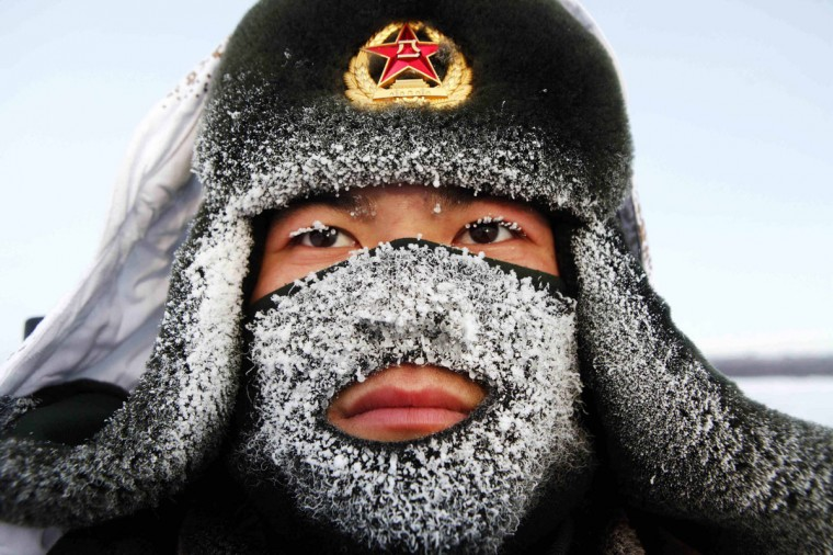 Frost covers the mask and part of the hat of a soldier of the People's Liberation Army (PLA) as he stand guard near the border of China and Russia in Heihe, Heilongjiang province. The local temperature reached -32 degrees Centigrade (-25.6 degrees Fahrenheit) on Wednesday. (Stringer/Reuters)