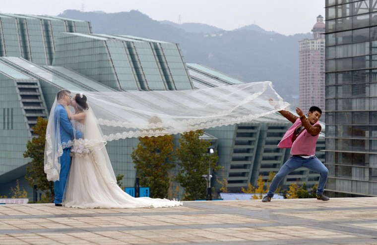 A newlywed couple kiss during a photo shoot, as an assistant runs away after lifting the veil, in Chongqing municipality, December 1, 2014. Picture taken December 1, 2014. (REUTERS/Stringer)