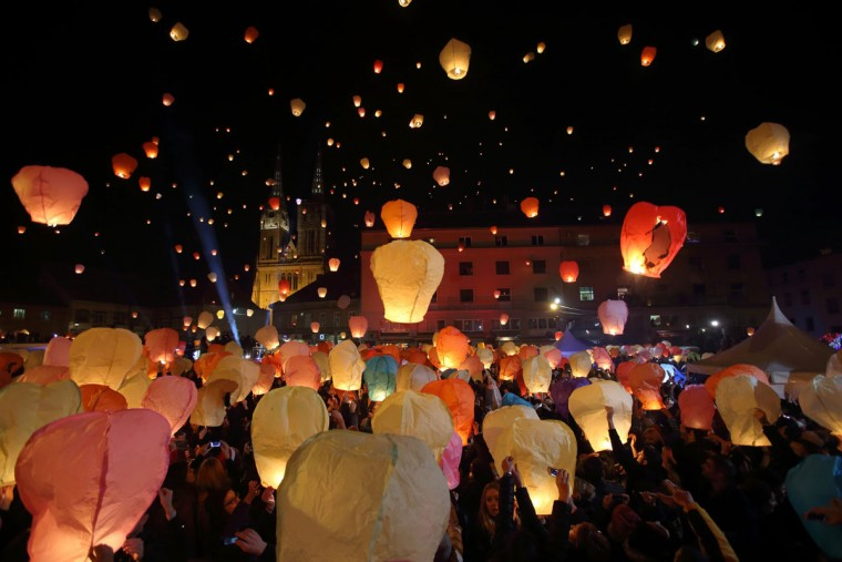 "A participant holds up a sky lantern to be released during the ""Kapulica & Lanterns"" event in Zagreb December 22, 2014. About 3000 participants attended the event, organized by contemporary artist Kresimir Tadija Kapulica as part of the ArtOmat Fair ahead of Christmas, which involved people releasing about a thousand lanterns to symbolize sending their wishes to the universe. (Antonio Bronic/Reuters)"