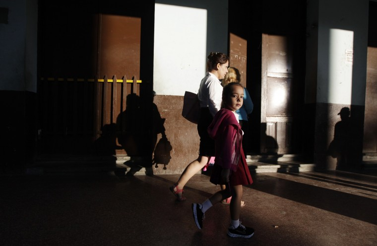A girl walks next to her mother early in the morning in Havana December 18, 2014. Cuban President Raul Castro hailed a landmark exchange of prisoners with the United States on Wednesday and praised U.S. President Barack Obama as the two countries agreed to normalize relations after more than five decades of hostility. REUTERS/Enrique De La Osa