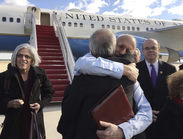 Alan Gross embraces Tim Rieser (C, back to camera), a member of Senator Patrick Leahy's office, on the tarmac as he disembarks from a U.S. government plane with wife Judy (L) at Joint Base Andrews in Maryland outside Washington December 17, 2014 in this photo courtesy of Jill Zuckman. The United States plans to restore diplomatic relations with Cuba more than 50 years after they were severed, a major policy shift after decades of hostile ties with the communist-ruled island, President Barack Obama said on Wednesday. Obama discussed the changes with Cuban President Raul Castro on Tuesday in a telephone call that lasted nearly an hour. Castro spoke in Cuba as Obama made his announcement on a policy shift made possible by the release of American Alan Gross, 65, who had been imprisoned in Cuba for five years. REUTERS/Jill Zuckman/Gross Family spokesperson/Handout via Reuters