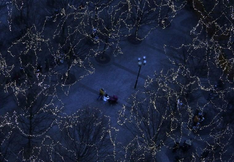 People walk under trees decorated with Christmas lights on the eve of Saint Nicholas Day at the Old Town Square in Prague December 5, 2014. (David W Cerny/Reuters)