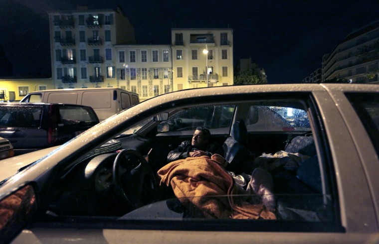 """Edy, a man who has been homeless for several years, tries to sleep in his car which is parked in a lot in Nice, southern France. Five homeless people have died since Saturday in France, alleged victims of the cold wave, a """"terrible litany"""" according to the Abbe Pierre Foundation, which reopens the debate on the """"poor housing"""" in the country. According to the INSEE national statistics office, the number of homeless has increased by 44% in France in 11 years. In 2012, 111,700 homeless people, including 31,000 children, were identified in the French medium and large cities, a report published last November by the office announced. (Eric Gaillard/Reuters)"""