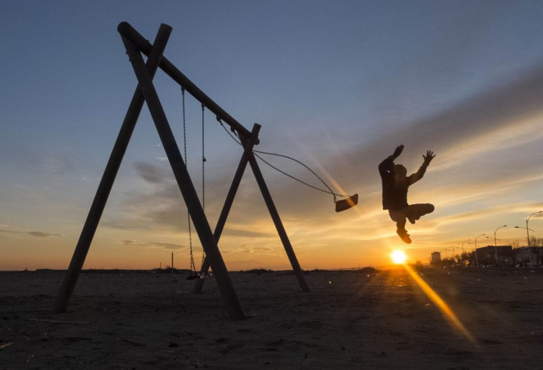 A boy jumps from a swing during sunset in Valras-Plage, southern France December 29, 2014. (Yves Herman/Reuters)