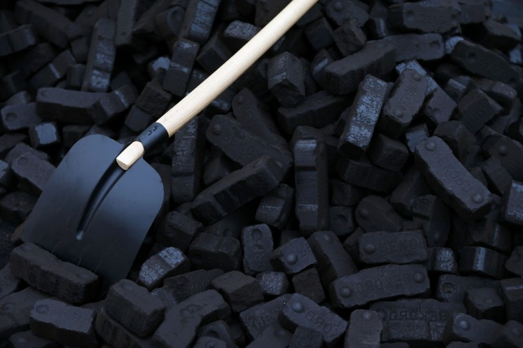 A shovel is placed over coal briquettes during a protest in front of the chancellery in Berlin December 3, 2014. Germany's cabinet will agree plans to cut CO2 emissions by up to 78 million tonnes by 2020, pushing operators to shut some coal-fired plants, to help Europe's biggest economy meet ambitious targets to fight climate change. The package, which also includes an energy efficiency program, is essential if Chancellor Angel Merkel is to avoid the embarrassment of missing her government's goal of a 40 percent reduction in emissions by 2020, compared to 1990 levels. REUTERS/Hannibal Hanschke
