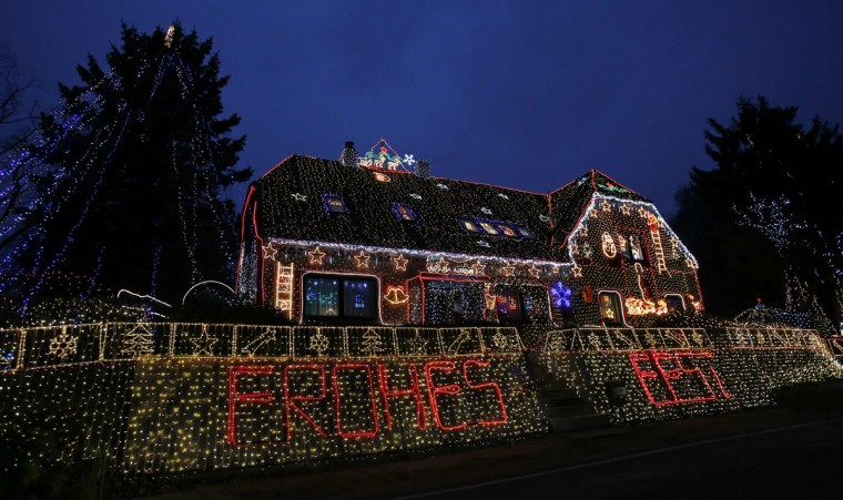 "An illuminated sign that says ""Merry Christmas"" is seen in front of a decorated house in the village of Calle, south of the northern German city of Bremen, December 2, 2014. Ralf Vogt, the 66 year-old owner of the so-called ""Lichterhaus"" (lights house) began decorating his house in early March this year. The power consumption of the some 450,000 Christmas lights comes up to 2,500 Euros (about $3,000) per its four-week season in December. Vogt started his tradition in the year 2000 with only 1,200 lights, following a vacation to the U.S. (Wolfgang Rattay/Reuters)"