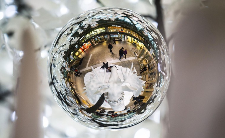 An elk as a part of a Christmas decoration is reflected in a Christmas ball ornament in a shopping mall in Berlin December 2, 2014. (REUTERS/Hannibal Hanschke)