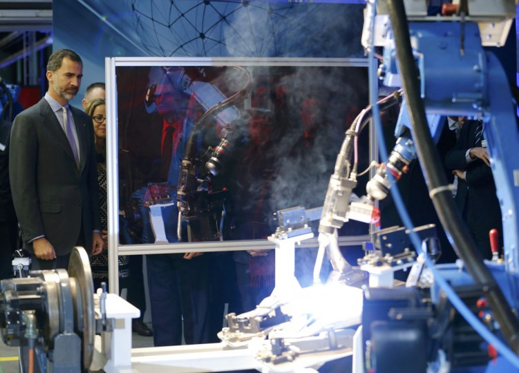 Spain's King Felipe (L) watches the work of a welding robot at Gestamp chassis innovation center in the western German city of Bielefeld December 2, 2014. (REUTERS/Wolfgang Rattay)