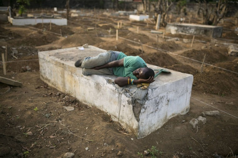 A grave digger sleeps near the graves of Ebola victims at a cemetery in Freetown, December 17, 2014. The death toll in the Ebola epidemic has risen to 6,915 out of 18,603 cases as of Dec. 14, the World Health Organization (WHO) said on Wednesday. There are signs that the increase in incidence in Sierra Leone has slowed, although 327 new cases were confirmed there in the past week, including 125 in the capital Freetown, the WHO said in its latest update. REUTERS/Baz Ratner
