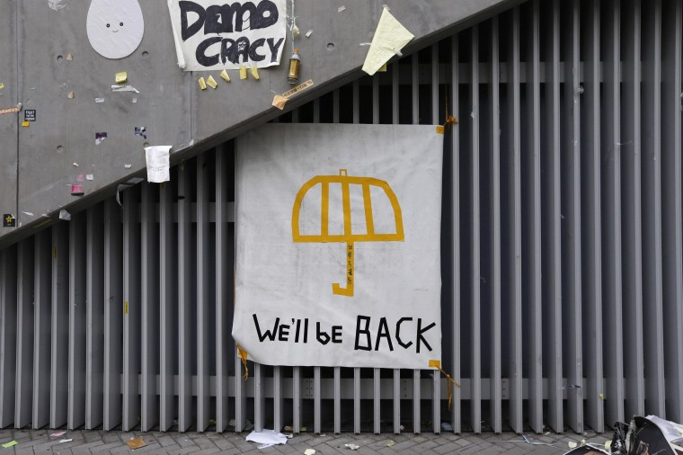 """A poster of an umbrella with the words """"We'll be back"""" written underneath is pictured on a wall at the main """"Occupy"""" protest site at Admiralty in Hong Kong December 11, 2014. Hong Kong police cleared most of the main protest site in December, marking an end to more than two months of street demonstrations in the Chinese-controlled city, but many chanted: """"We will be back"""". Protest leaders have said they will consider other forms of civil disobedience, given Beijing's continued refusal to grant any concessions. Picture taken December 11. REUTERS/Bobby Yip"""