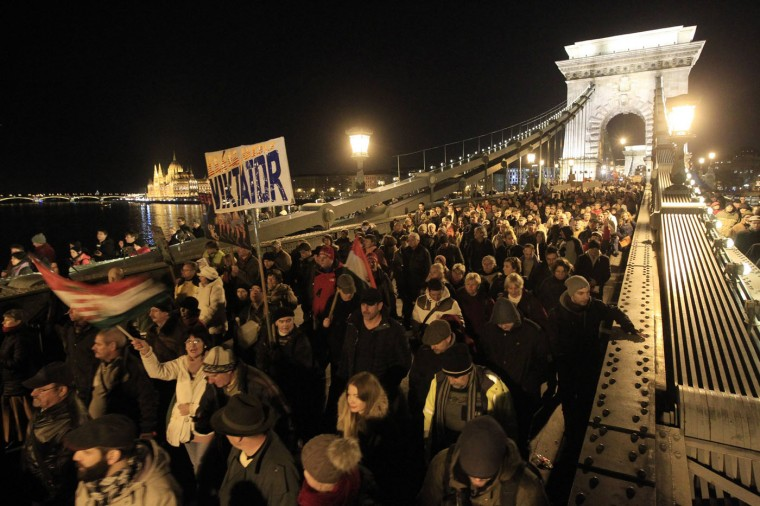 Thousands of people march at Chain Bridge as they protest against what they say is corruption within the country's tax authority as well as a lack of wider democratic freedoms, in front of the Hungarian parliament in Budapest December 4, 2014. REUTERS/Bernadett Szabo
