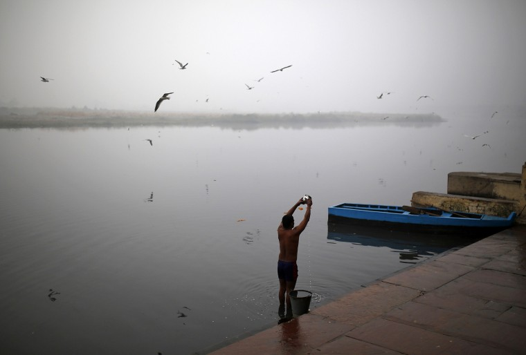 A Hindu devotee prays to the Sun god as he stands in the waters of the river Yamuna on a cold, winter morning in New Delhi December 18, 2014. REUTERS/Ahmad Masood