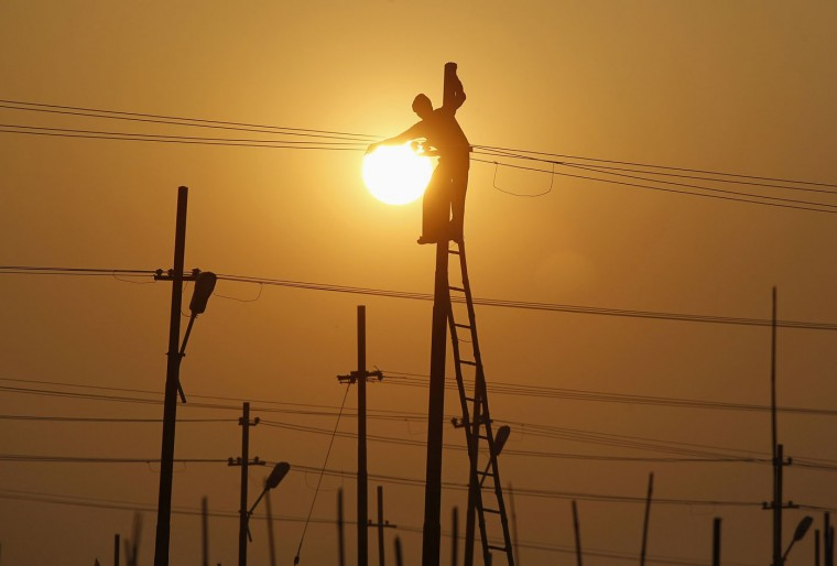 A worker is silhouetted against the setting sun while installing an overhead electric cable pole on the banks of river Ganges in the northern Indian city of Allahabad December 26, 2014. REUTERS/Jitendra Prakash