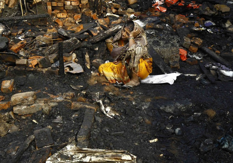 Taramuni Ray, 62, cries as she sits on the debris from her burnt hut after a fire occurred at a slum in Kolkata December 4, 2014. Several huts were gutted in the fire but no casualties were reported and the cause of the fire was unknown, local media reported on Thursday. REUTERS/Rupak De Chowdhuri